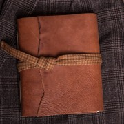 This is a tan leather journal that is made by Trekker Leather Co, notice the plaid lace it is tied off with