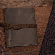 This is a green leather journal with a plaid lace from Trekker Leather Co