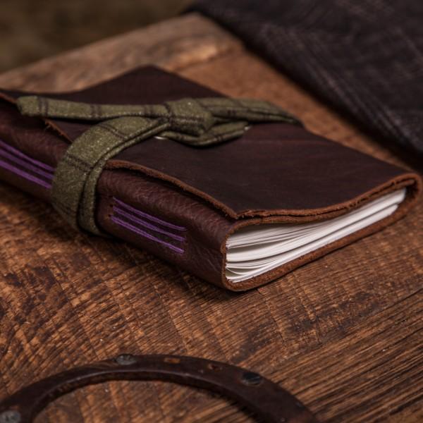 The Brazilian Kodiak Journal with purple bamboo stitching, and green plaid.