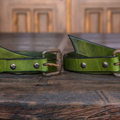 The Green Leather Belt by Trekker Leather Co two coiled up next to each other.