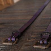Two Purple Leather Belts by Trekker Leather Co focused in on the rusty belt buckles